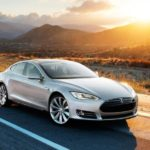 grey Tesla model S driving on the road with the sun setting in the background